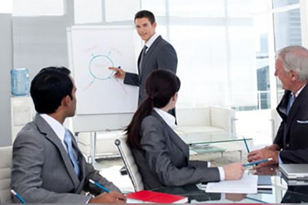 man in a suit standing next to a white board explaining a diagram to three other business people seated at a table.